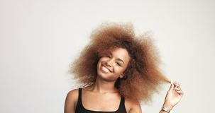 Beuayt black woman with a huge afro hair having fun smiling and touching her hair