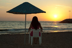 beundra den sittande solnedgångkvinnan för stolen Arkivfoto