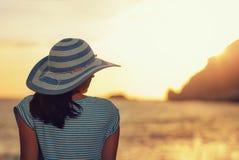 Beundrar den bärande hatten för kvinnan solnedgången över havet arkivbilder