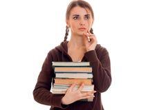 Beunruhigendes junges Mädchen-jugendlich mit Zöpfen hält in ihrer Hand viele Bücher und blickt in Richtung Stockbilder