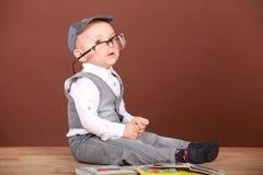 Beunruhigendes Kind, das auf dem Boden in den Gläsern mit Büchern sitzt Stockfoto