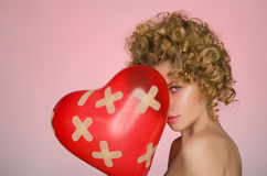 Beunruhigte Frau mit Ball in Form des Herzens Stockfoto