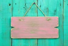 Beunruhigtes rosa leeres Zeichen, das an der antiken grünen Holztür hängt Lizenzfreie Stockfotos