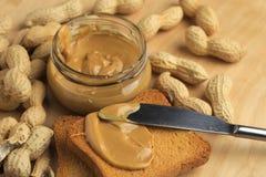 Beurre d'arachide avec des biscottes Photos stock