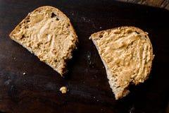 Beurre d'arachide crémeux avec du pain sur le conseil en bois photographie stock libre de droits