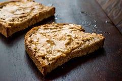 Beurre d'arachide crémeux avec du pain sur le conseil en bois images stock