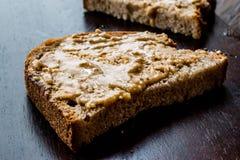 Beurre d'arachide crémeux avec du pain sur le conseil en bois photos stock