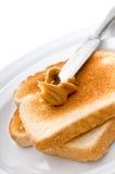Beurre d'arachide de propagation sur le pain grillé image stock