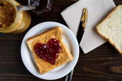 Beurre d'arachide et sandwich en forme de coeur à gelée Photos stock