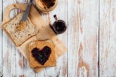 Beurre d'arachide et sandwich faits maison à gelée sur le fond en bois Images libres de droits
