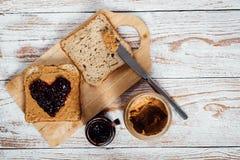 Beurre d'arachide et sandwich faits maison à gelée sur le fond en bois Photographie stock