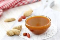 Beurre d'arachide sur un bol en verre Photos stock