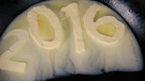 Beurre dans la forme du numéro 2016 fondant sur la casserole chaude - fermez-vous vers le haut de la vue supérieure banque de vidéos