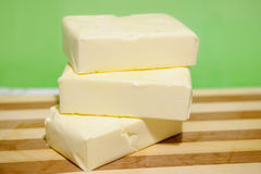 Beurre dans les briquettes sur un hachoir Photo stock