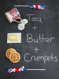 Beurre et crumpets de thé sur un tableau noir avec les drapeaux britanniques Image libre de droits