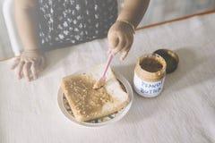 Beurre jouant/de propagation de bébé asiatique d'arachide sur un pain Photographie stock