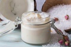 Beurre pour le corps de la noix de coco et des roses photographie stock
