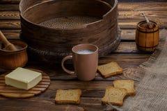 Beurrez le pain grillé, le miel et le lait sur le backgraund en bois Image stock