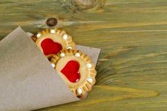 Beurrez les biscuits sablés bourrés de la gelée en forme de coeur rouge dans le sac de papier roulé sur la table en bois brune Photo libre de droits