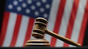 Beurteilen Sie ` s hölzernen Hammer auf Block gegen die amerikanische Flagge, die in USA-Gericht wellenartig bewegt stock video footage