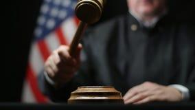 Beurteilen Sie ` s Hand, die einen Hammer auf Block gegen amerikanische Flagge in Gericht Vereinigter Staaten schlägt stock footage
