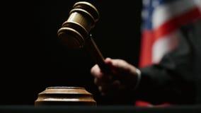 Beurteilen Sie ` s Hand mit hölzernem Hammer gegen Schwarzhintergrund der amerikanischen Flagge in USA-Gericht stock video