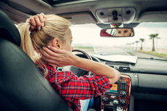 Beutiful blond girl comb her hair with a rearview mirror in car Royalty Free Stock Image