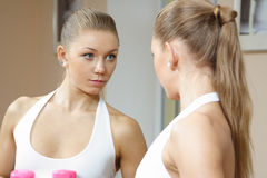 Beutiful blonde girl looking in mirror fitness gym. Beautiful Girl in Fitness Gym Photoshoot. More images of this models you can find in my portfolio Stock Photography