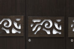 Beutiful contemporary modern looking design on a wardrobe door made of dark Brown coloured plywood. White pattern chiseled on a dark plywood door of a three door Royalty Free Stock Photo