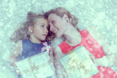 Beutiful gift blinkers. Mother daughter with presents lying down Stock Images