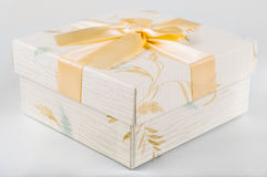 Beutiful gift box with flowers and golden ribbon. On a white background Royalty Free Stock Photography