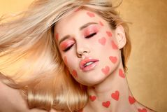 Beutiful girl portrait with coral color hearts makeup.  royalty free stock photography