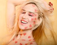 Beutiful girl portrait with coral color hearts makeup. Smiling royalty free stock image