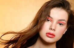 Beutiful girl portrait with coral color makeup. And wind stock image