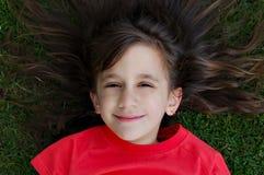 Beutiful girl smiling in the grass. Beautiful girl smiling while laying in the grass Royalty Free Stock Photo