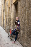 Beutiful happy woman in a small alley, street with an old bike Royalty Free Stock Photos