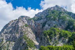 A beutiful landscape in the mountains, clouds above peaks and forest in foreground Royalty Free Stock Image