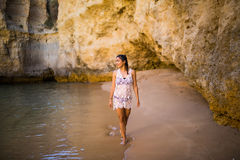 Beutiful latin mexican girl tourist walking  on beach with rocks. On beautiful beach near ocean in  portugal Royalty Free Stock Photography