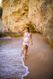Beutiful latin mexican girl tourist walking  on beach with rocks. On beautiful beach near ocean in  portugal Stock Image