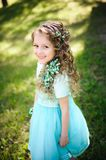 Beutiful little girl smiling looking at camera in the blooming spring garden royalty free stock image