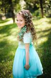 Beutiful little girl smiling looking at camera in the blooming spring garden stock photography