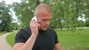 Beutiful muscular man talking by the phone in park stock video footage