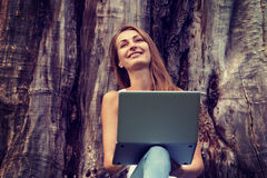 Beutiful student girl working on her laptop outdoor at sunny day Stock Image