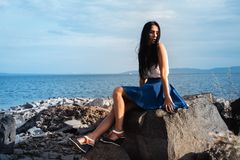 A woman sitting on a rock royalty free stock images