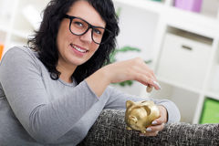 Beutiful woman sitting on the sofa and puts coin in a piggy bank Stock Photo