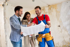 Beutiful young couple looking blueprints of their home with hand Royalty Free Stock Images