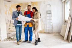 Beutiful young couple looking blueprints of their home with hand Royalty Free Stock Photo