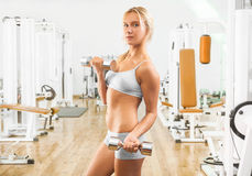 Beutiful young girl wearing working clothes lifting weights in g Royalty Free Stock Photos
