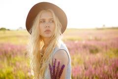 Beutyportret van het schitterende blondemeisje dragen in hoed buiten het stellen, dat op een bloemengebied, op zonsondergangachte royalty-vrije stock fotografie