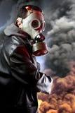 Beväpnad man med gasmasken över explosionbakgrund arkivbild